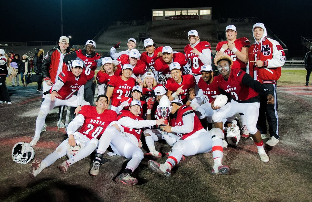 A few of the North Gwinnett Seniors pose with the trophy after winning the Class AAAAAAA State Championship game at North Gwinnett.    Photo Courtesy Nicole Seitz