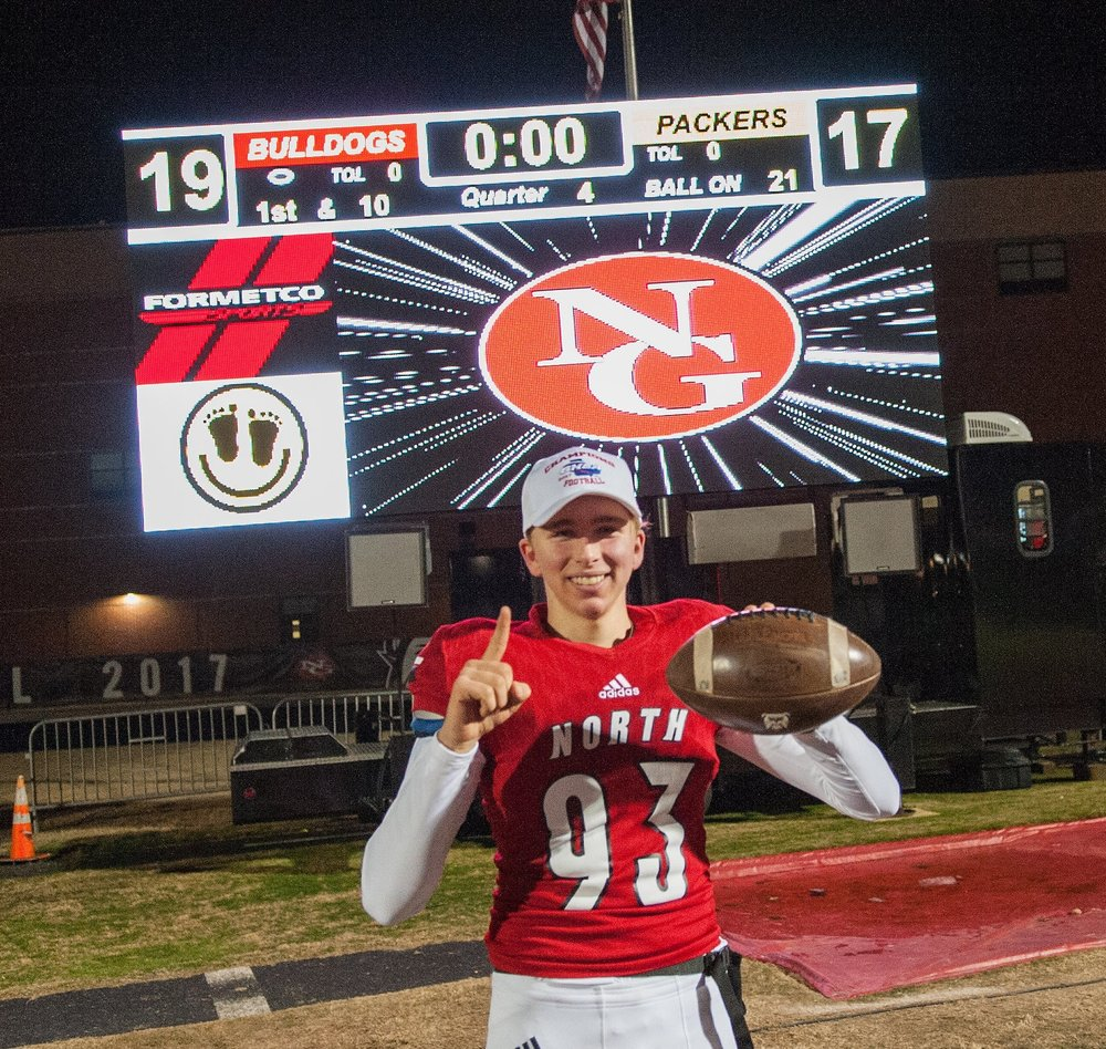 North Gwinnett's Cameron Clark (93) poses in front of the scoreboard after his game winning field goal at the GHSA Class AAAAAAA Championship game at North Gwinnett.  Photo Courtesy Nicole Seitz