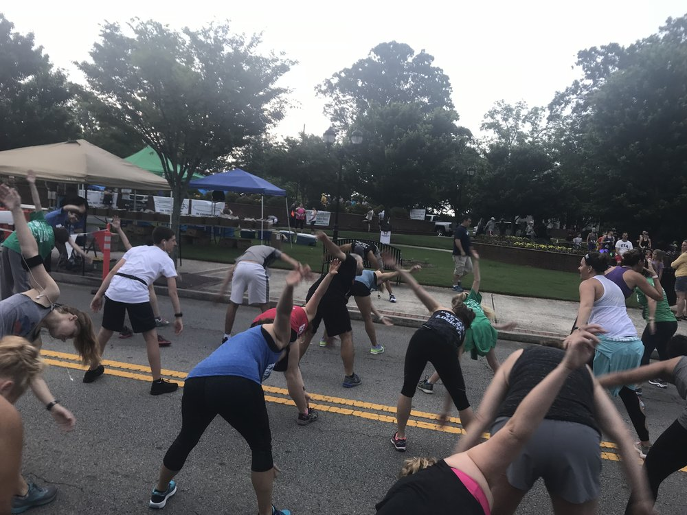 Runners stretching to get warmed up before the start of the 5k. Photo courtesy of Jillena Smith.