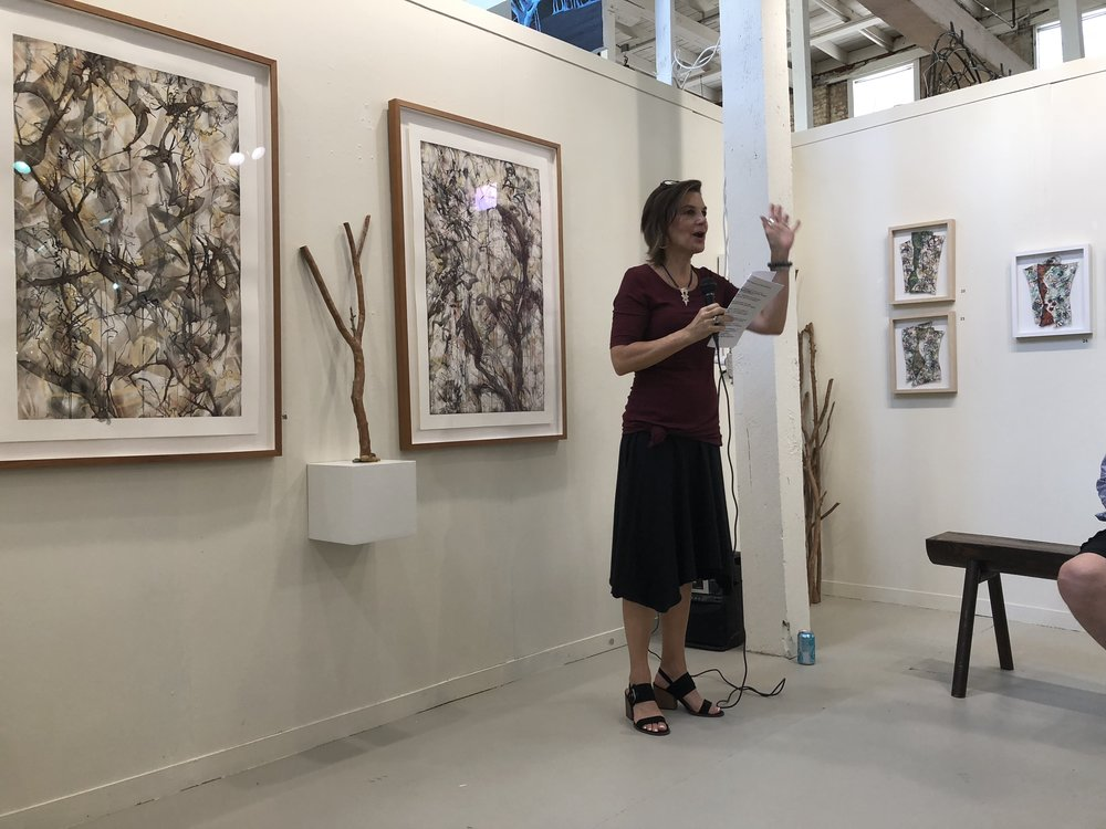 Artist Roxane Hollosi talks about her artwork to attendees of the opening reception for the new Tannery Row Artist Colony Art Exhibit featuring her work. Photo credit: Katiee McKinstry