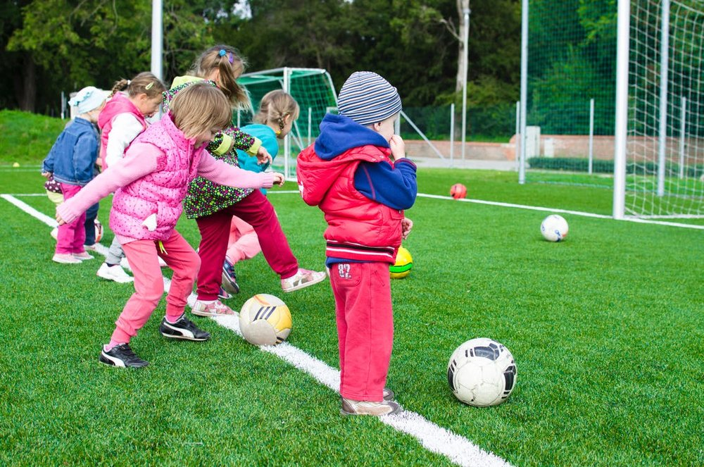 Children kicking soccer balls outside on field
