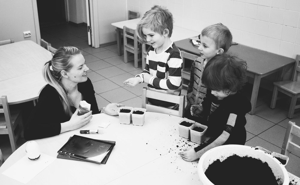 Teacher and three students at table looking at dirt