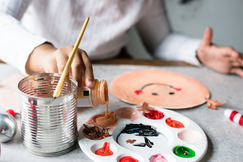 Child pouring skin-colored paint into palette, painting a face