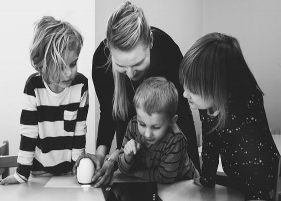 Teacher with three students looking at a tablet
