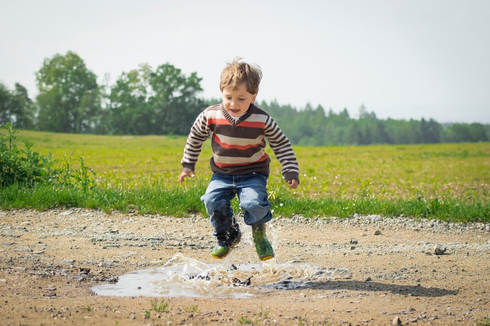 Boy wearing rain boots and jumping mud puddle