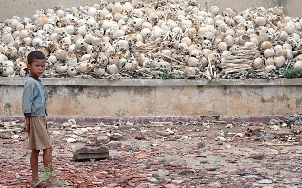 A Cambodian boy stands infront of a platform covered with human skulls at the Killing Field in Trapeang Sva Village, Kandal province