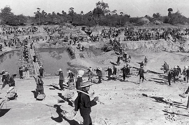 Workers planting rice and building bridges