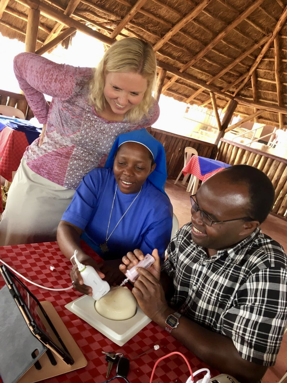 Dr. DeStigter, Sister Angela, and Dr. Alphons practicing with some new portable ultrasound units for breast biopsies along the banks of the Nile River.