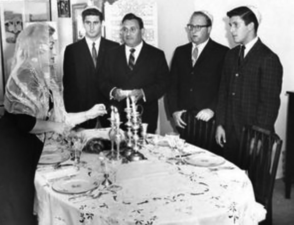 My mother lighting the candles on the Shabbos Eve in our home in Great Neck, Long Island, with ( left to right ) me, my father, and my brothers Barry and Henry.  (From the personal collection of David N. Tucker)