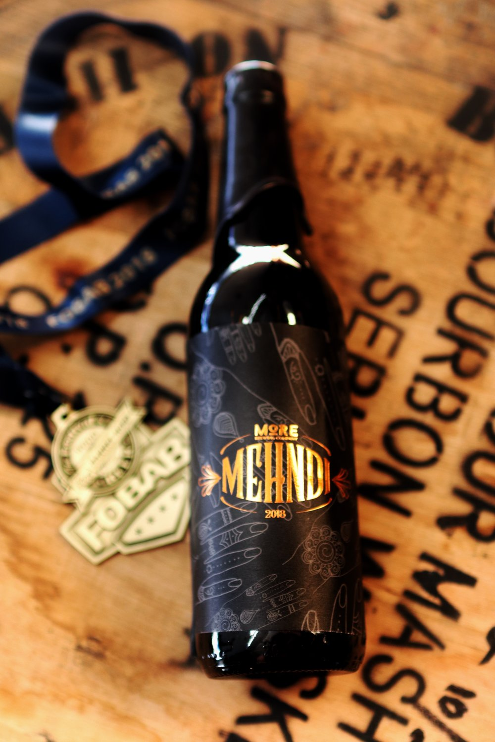 Mehndi (2018) - CLICK HERE TO ENTER THE LOTTERY FOR 2018 MEHNDIReleased: 11/23/201814.5% ABVBarrels: Four Roses, Old Weller Antique, Russell's ReserveRest Time: 15 monthsAccolades:- 2018 Festival of Wood & Barrel-Aged Beer (FoBAB) - Gold Medal - Strong Porter/StoutMehndi 2018 is our expression of nuance. We took a robust imperial stout and aged it in a blend of hand-selected bourbon barrels that we sourced from Warehouse Liquors in Chicago, IL. We let the beer age for 15 months, in a mildly temperature controlled environment. Doing this, let the barrels come to life and breathe with the changing seasons and temperatures. The resulting beer, is a true expression of our craft. Flavors of dark fudge, intermingle with notes of vanilla, and subtle, savory smokiness from the charred oak it rested in.Mehndi exemplifies what patience can achieve. We will release Mehndi once a year and plan to release a