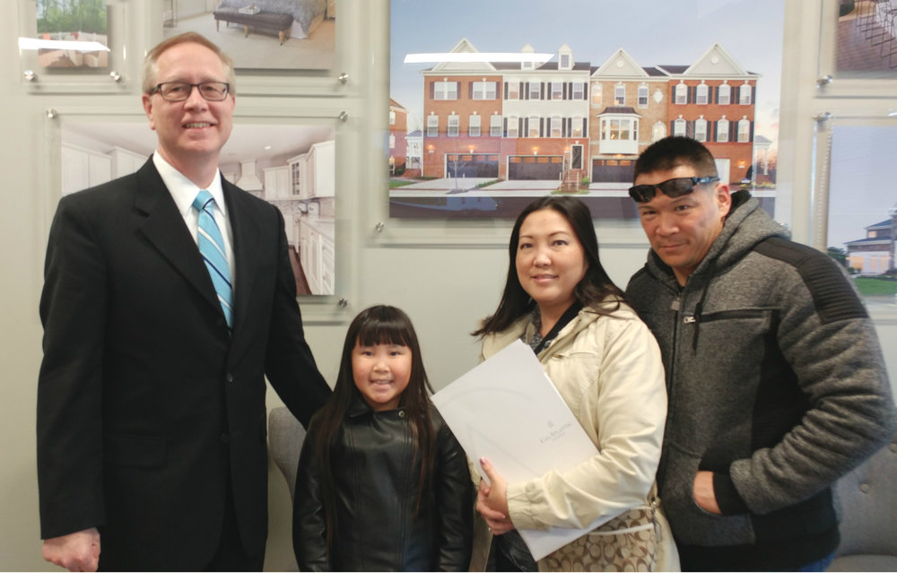 Jerry Kline (left), Realtor with Keller Williams Flagship of Maryland, celebrates with Travis, Leslie and Jenna on the purchase of their new-construction home in the greater Fort Meade, Maryland, community of Glen Burnie. The family just relocated from Hawaii, and moved into their new home just in time for Jenna to see her first snowfall!