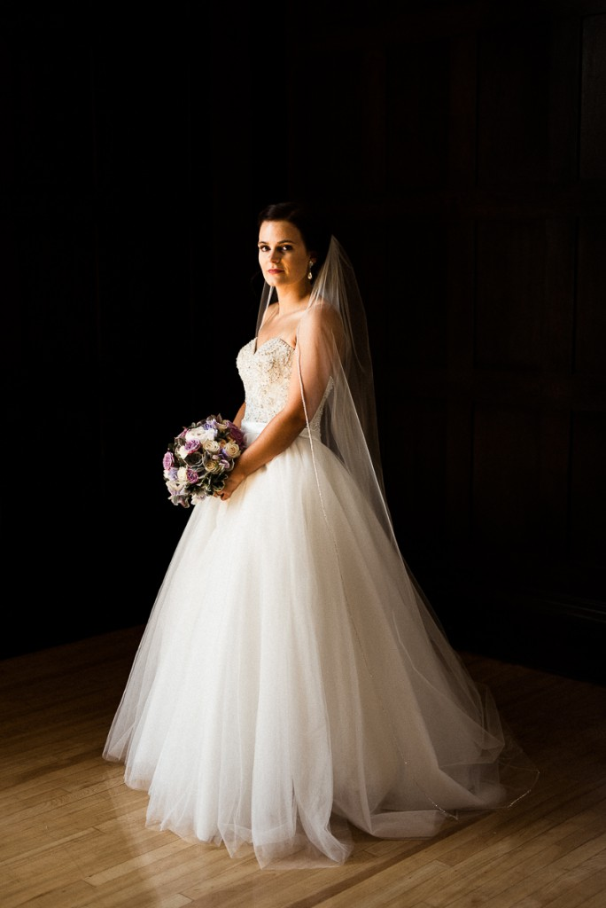 Beautiful bride in a tulle ballgown at the bride and groom pose for portrait outside of the Minneapolis club