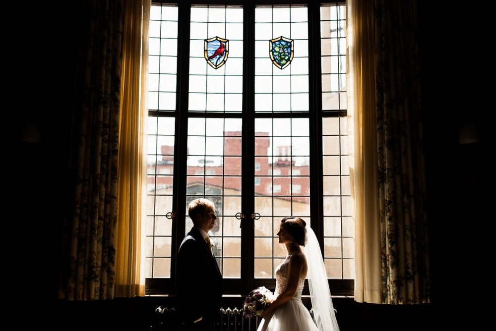 Indoor portrait of bride and groom in front of large window at bride and groom pose for portrait outside of the Minneapolis wedding venue, bride and groom pose for portrait outside of the Minneapolis club