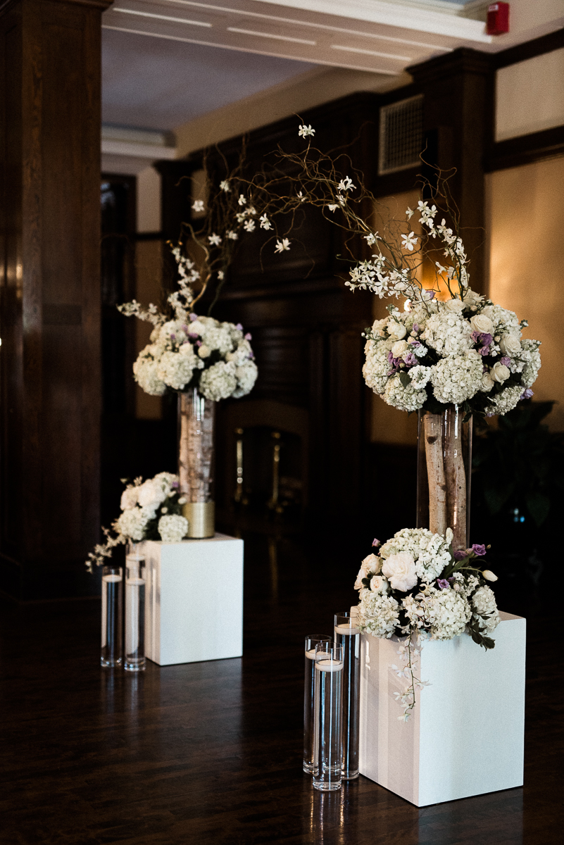 Largewhite with purple accents floral arrangements at the alter for wedding ceremony at Minneapolis club