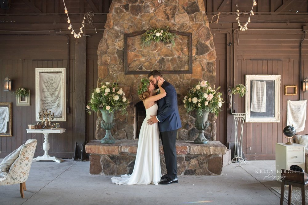 Bride and groom embrace in front of rustic fireplace at Historic Hope Glen Farm