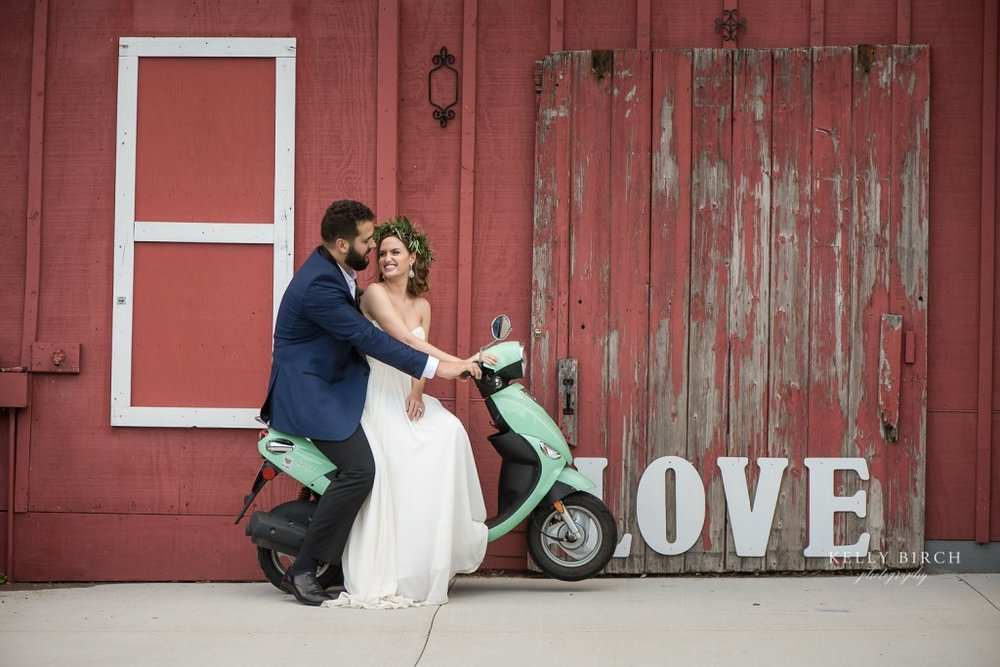 Couple in front of Historic Hope Glen Farm barn on a teal vespa