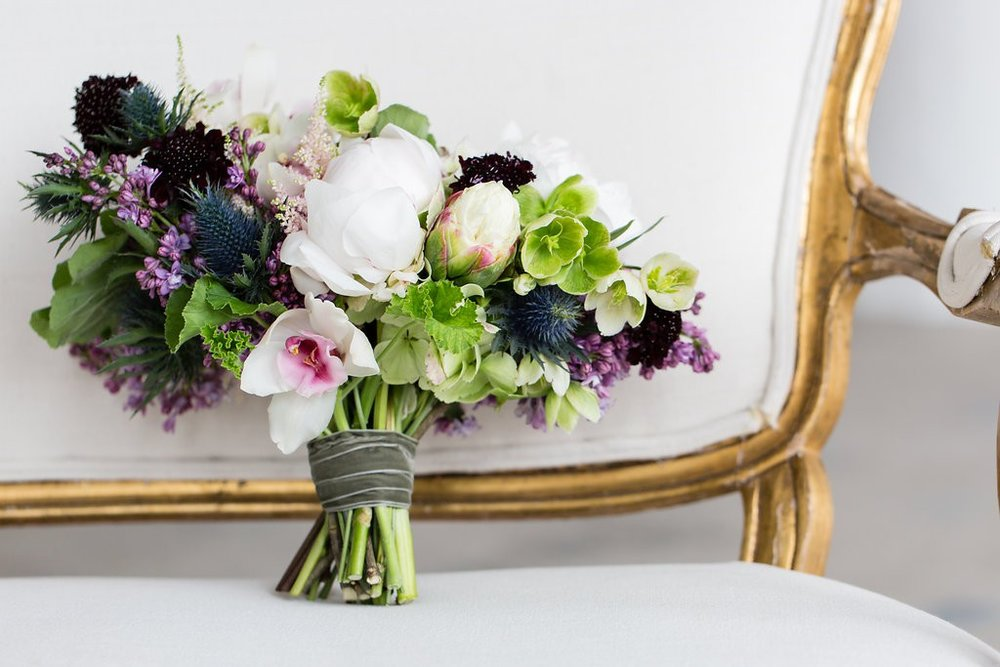 Garden style bouquet in shades of green, purple, white and deep navy blue