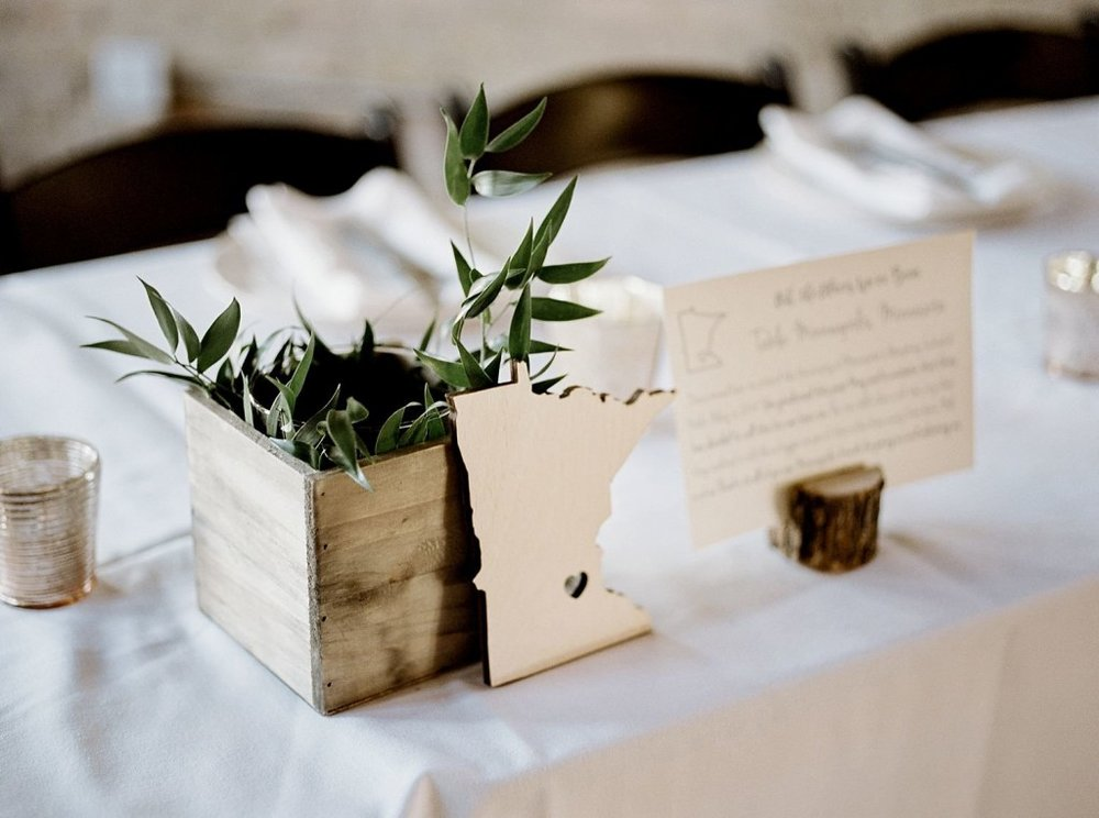 Table number and minimal centerpice with greenery and rustic tones