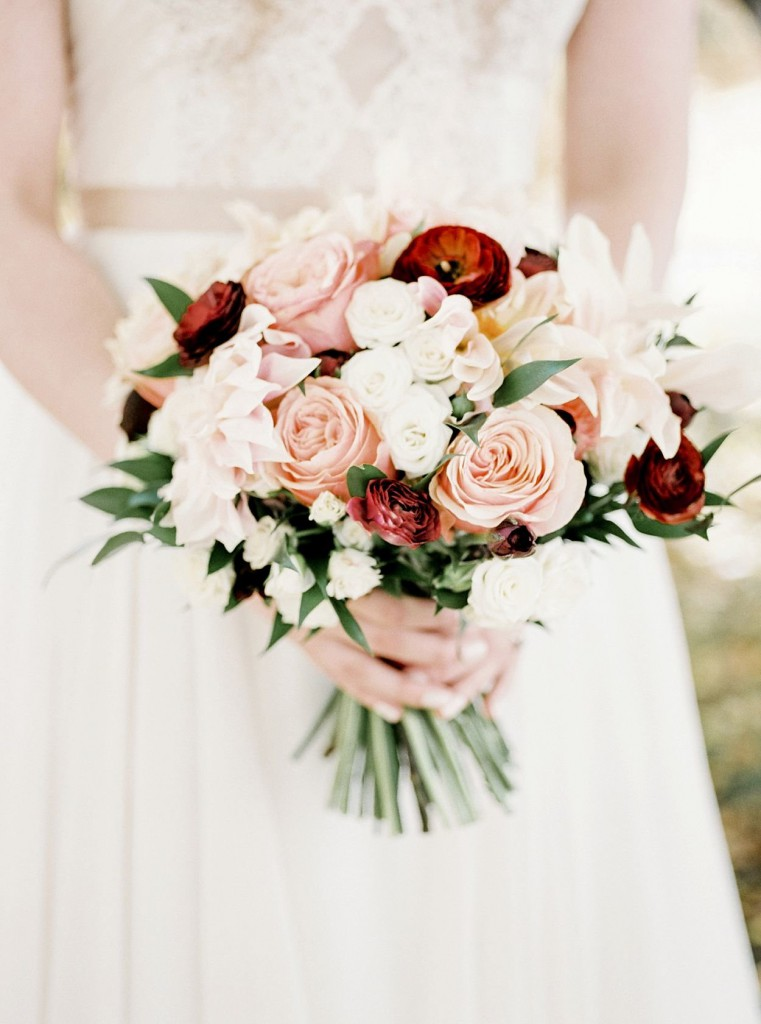Bridal bouquet made with Fall florals in pink, peach and red shades with Dahlias, roses, hydrangea, greenery