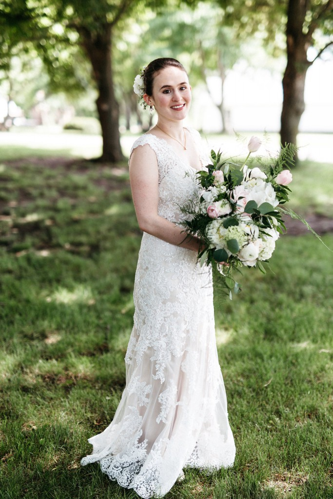 Bride in lace wedding dress and large blush, white, greenery bouquet at Red Barn Farm