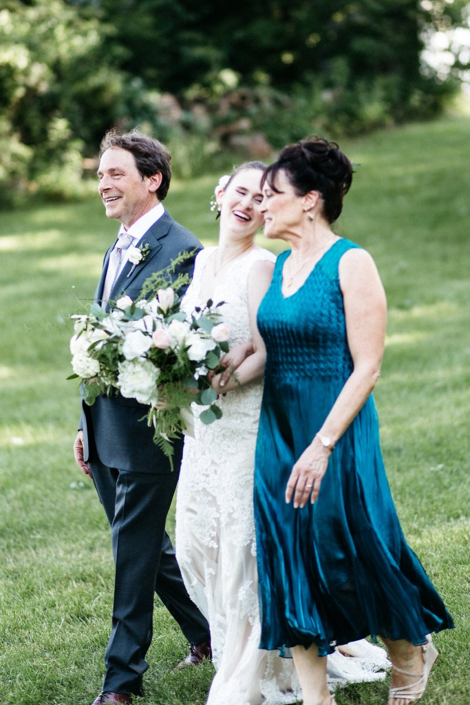 bride walking down the aisle with parents for outdoor wedding at Red Barn Farm