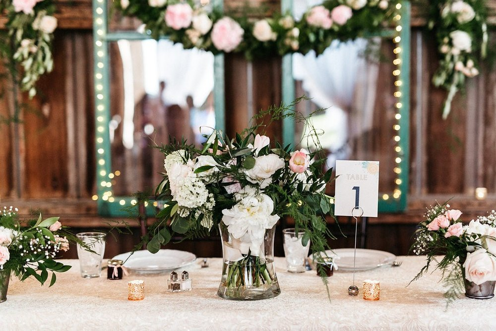 Lovely centerpiece of white and blush florals at head table