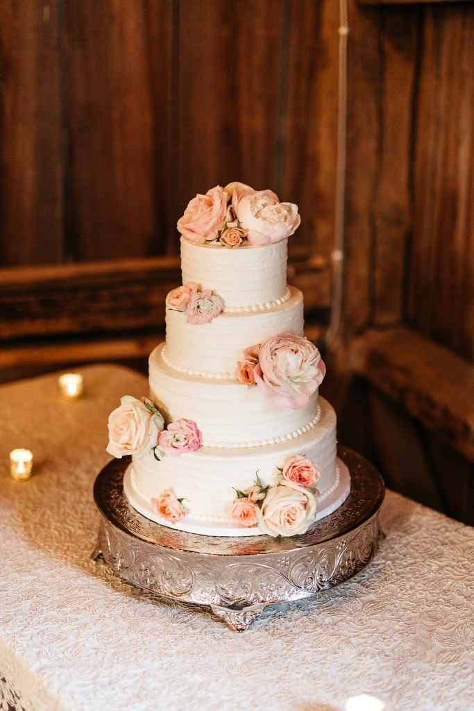 four tier white wedding cake with fresh blush florals