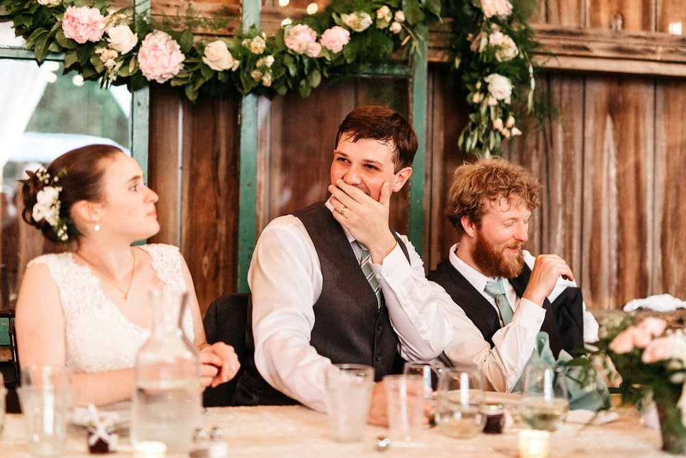 toasts at wedding reception- groom laughing
