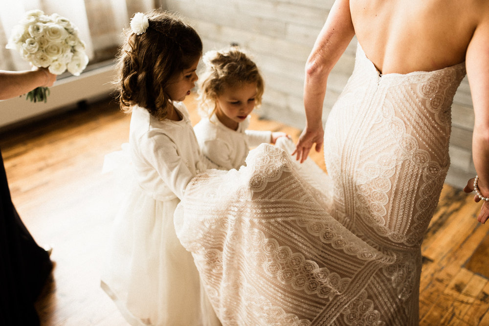 flower girls helping the bride with her dress