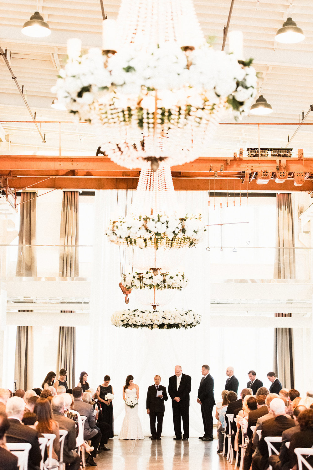 wedding ceremony with hanging floral chandeliers