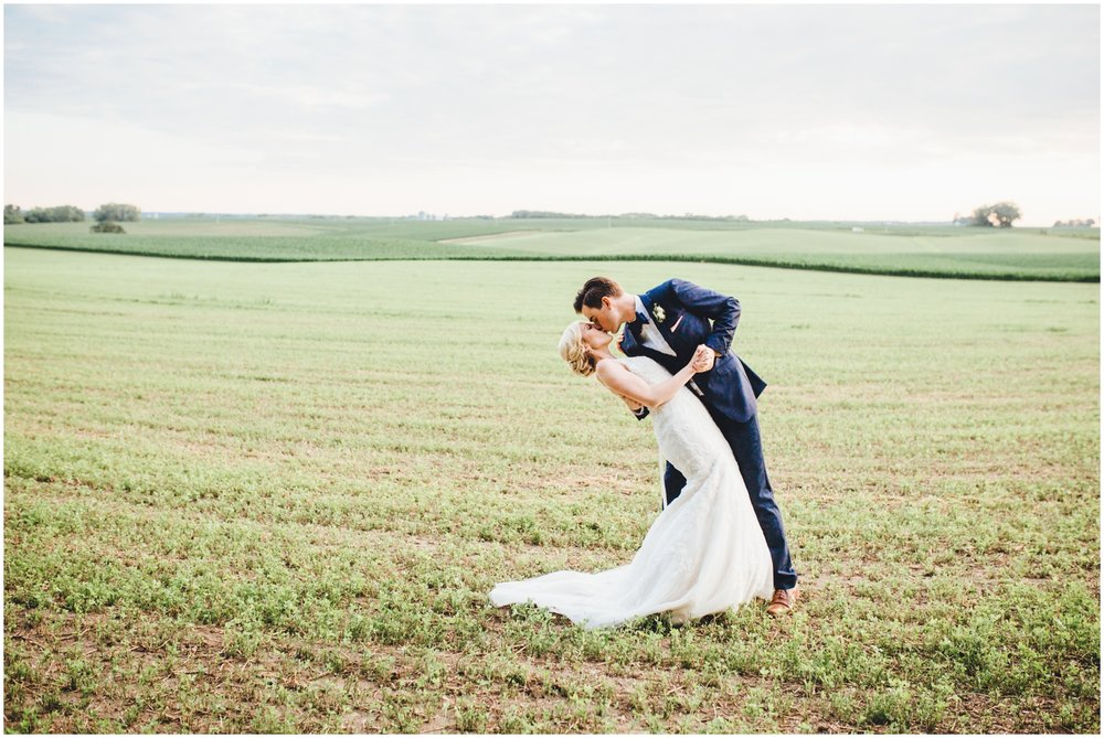 bride and groom kiss in a field