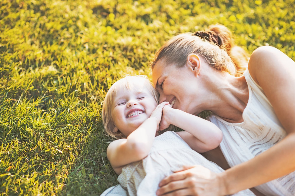 Mother and toddler laughing together in the summer grass, joyful parenting, CBT to support strong families