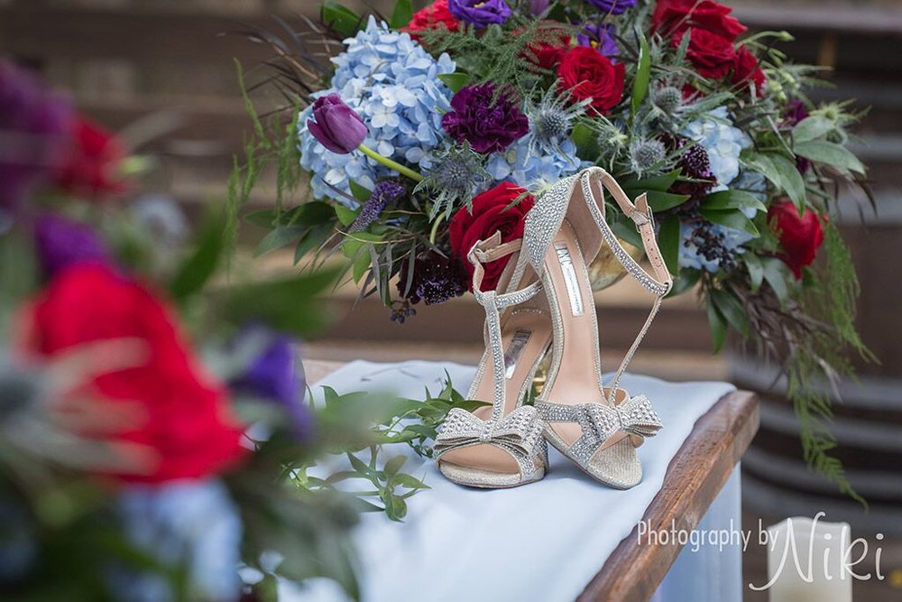 wedding shoes with red rose and blue hydrangia bouquet.jpeg