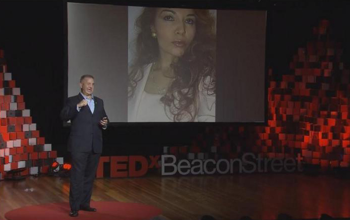 Justin Constantine at his Tedx Talk wit my photo as he talks about my stories of survival