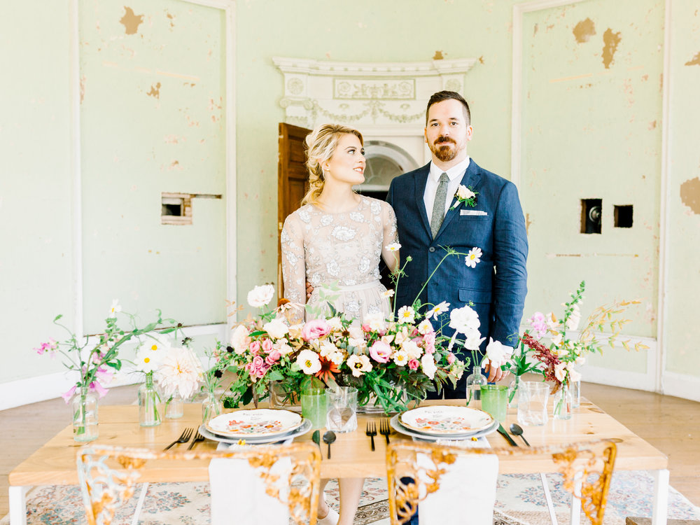 Emily and Jake pose in front of the wild and whimsical tablescape from this Woodlands Mansion elopement wedding inspiration.
