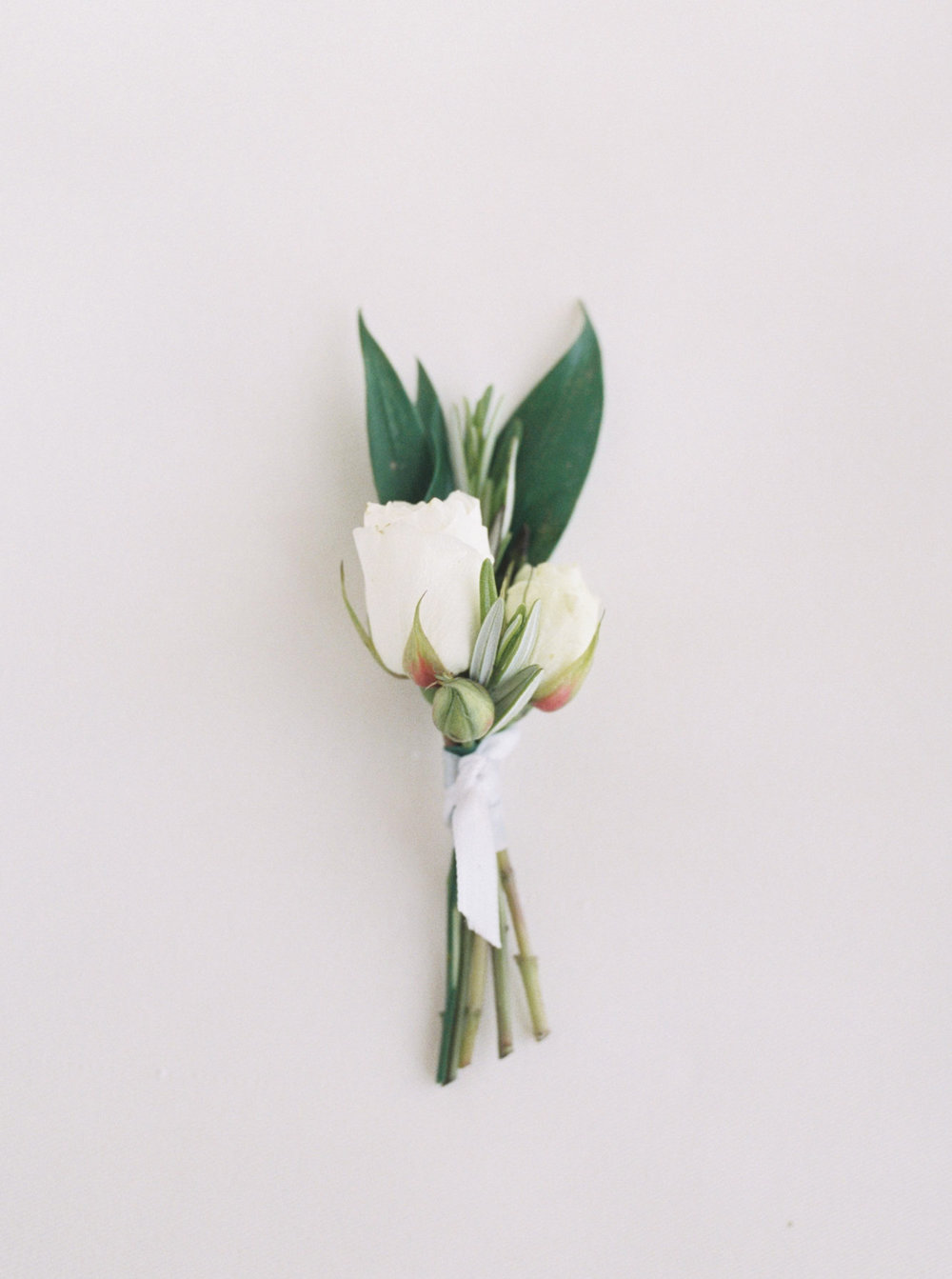 A sweet, simple, and delicate white rose boutonniere for a classic and minimal floral touch on your wedding day.