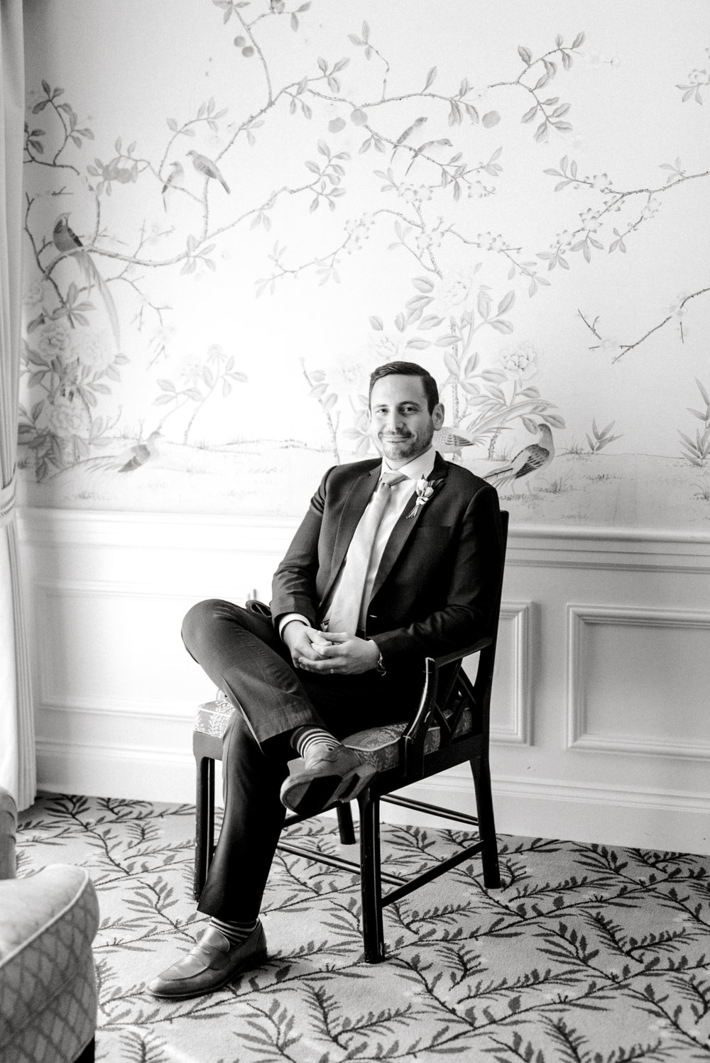 The handsome groom relaxing in a patterned room at the Baltimore Country Club the morning of his wedding.