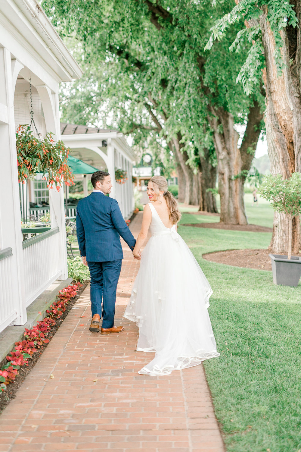 Kerry and Bill smile stroll along the brick path at the Baltimore Country Club on their Italian themed wedding day.