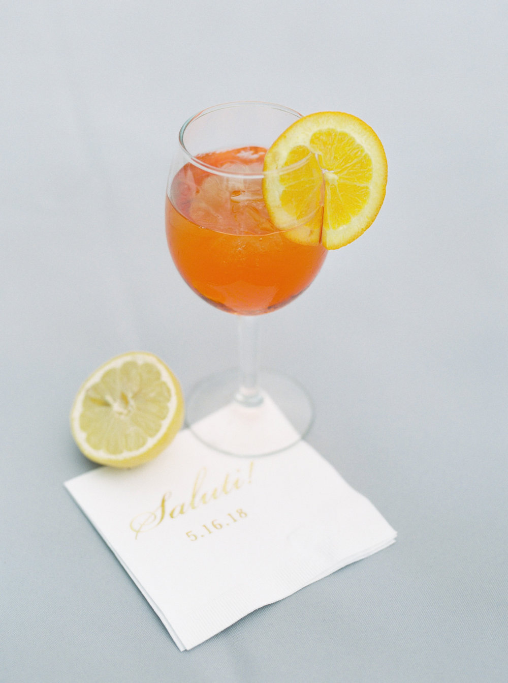 This bright citrus signature cocktail from Kerry and Bill's Italian themed wedding day at the Baltimore Country Club is so fun. We love the pop of orange and yellow against the neutral whites of the tented space.