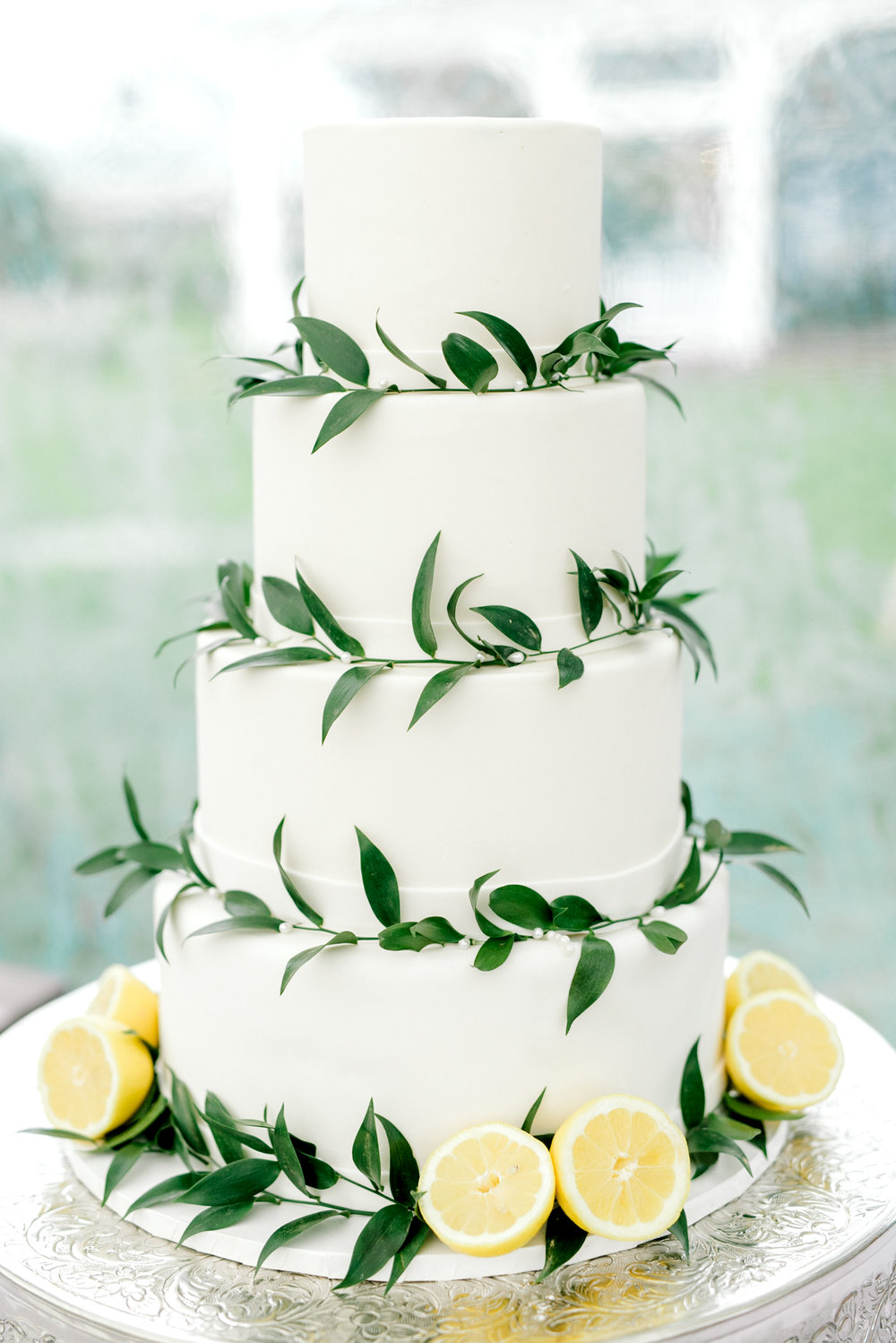 This minimal white wedding cake with lemon accents is so simple and elegant that we're swooning. It's the perfect sweet for your elegant and bright Italian themed wedding day.