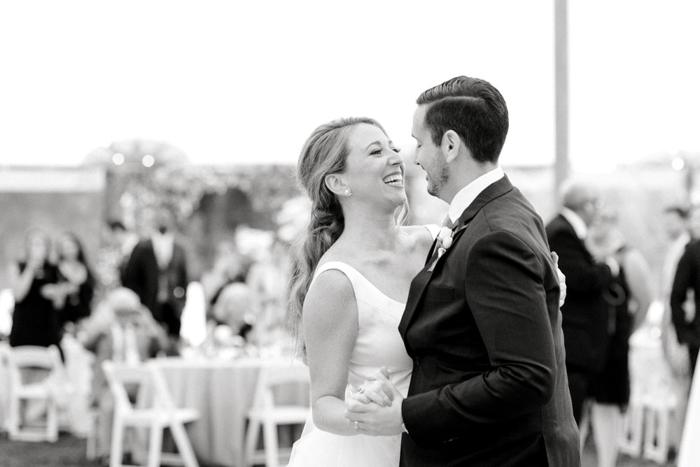 Kerry and Bill laugh during their first dance under the sail pole tent during their Italian inspired summer lemon wedding at the Baltimore Country Club.