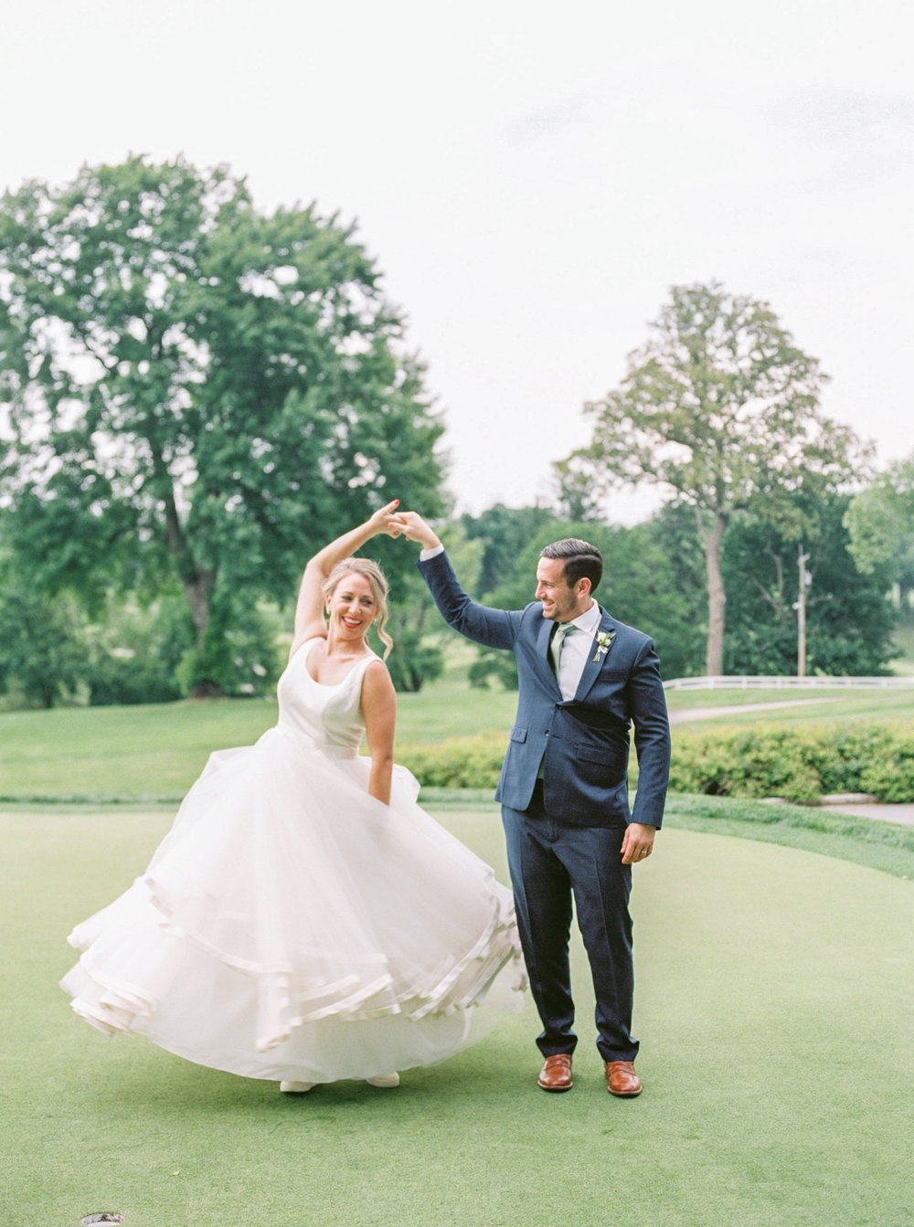 Bill twirls his girl on the green at the Italian inspired summer lemon wedding at the Baltimore Country Club.