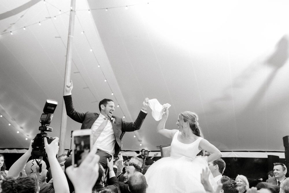 The fun and excitement is palpable as Kerry and Bill are hoisted in the air during the Hora under the sail pole tent from their Italian inspired summer lemon wedding at the Baltimore Country Club.