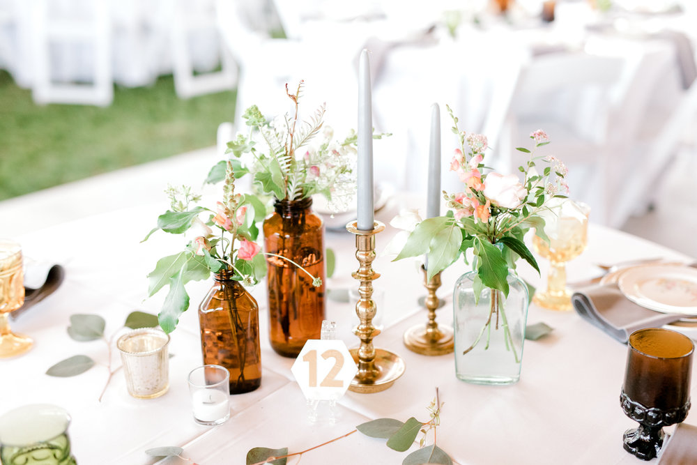 haley-richter-photography-summer-winery-vineyard-wedding-gold-glass-bottle-centerpiece-wildflowers-pink-and-white-stone-table-numbers-whimsical-blue-candles