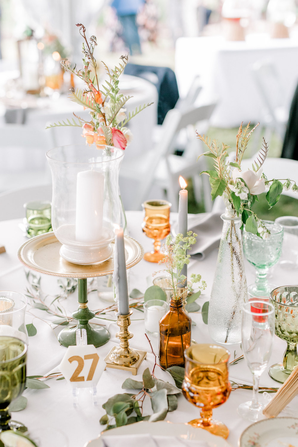 haley-richter-photography-ecclectic-glass-bottle-centerpiece-whimsical-table-candles-gold-candlesticks-blue-candles-glass-goblets-stone-gold-table-numbers
