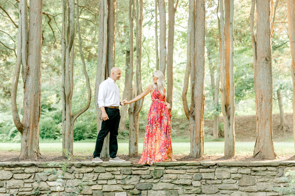 Liz leads Bill through the wooded garden with the sunlight pouring through the trees for their romantic sunset woodland engagement session at Parque at Ridley Creek.