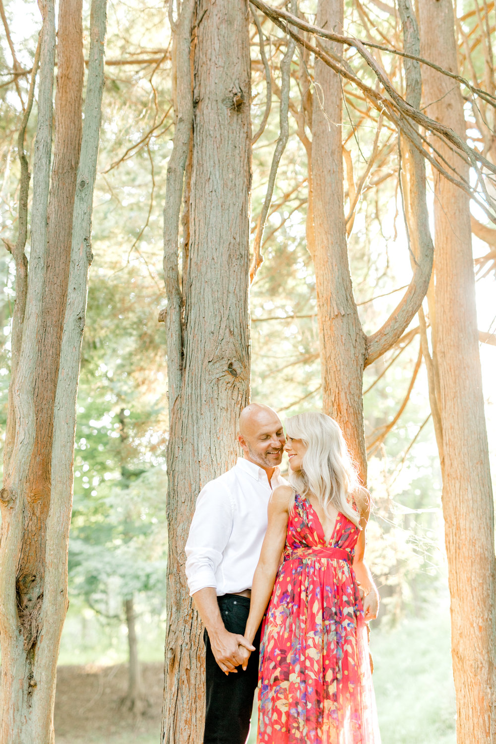 Liz and Bill get close for an intimate moment at their romantic sunset woodland engagement session at Parque at Ridley Creek