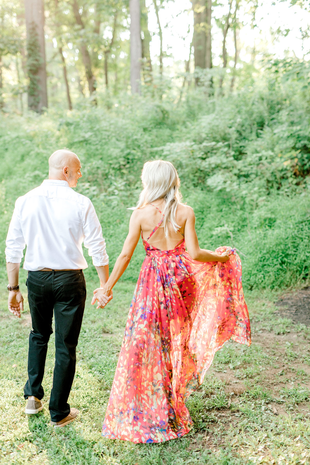 And they're off, hand in hand during their romantic sunset woodland engagement session at Parque at Ridley Creek