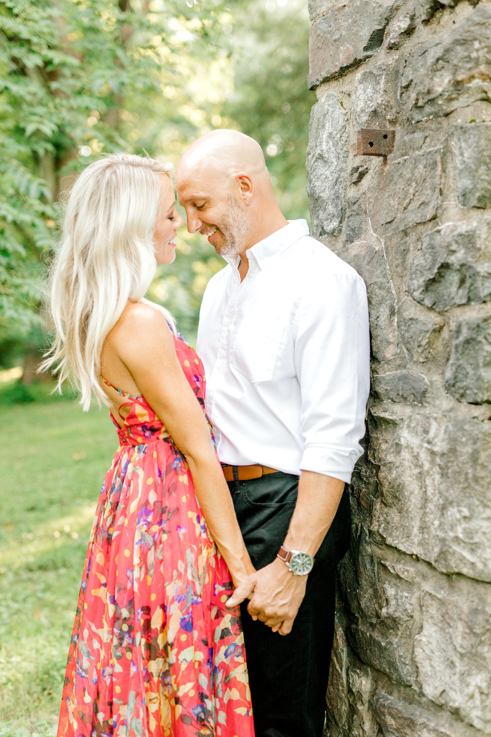 All snuggled up, we love the way Liz's bright red dress pairs with Bill's neutral color palette of black and white. The pop of floral print in the dress brings this classic color combo right into the summer for their romantic sunset woodland engagement session at Parque at Ridley Creek