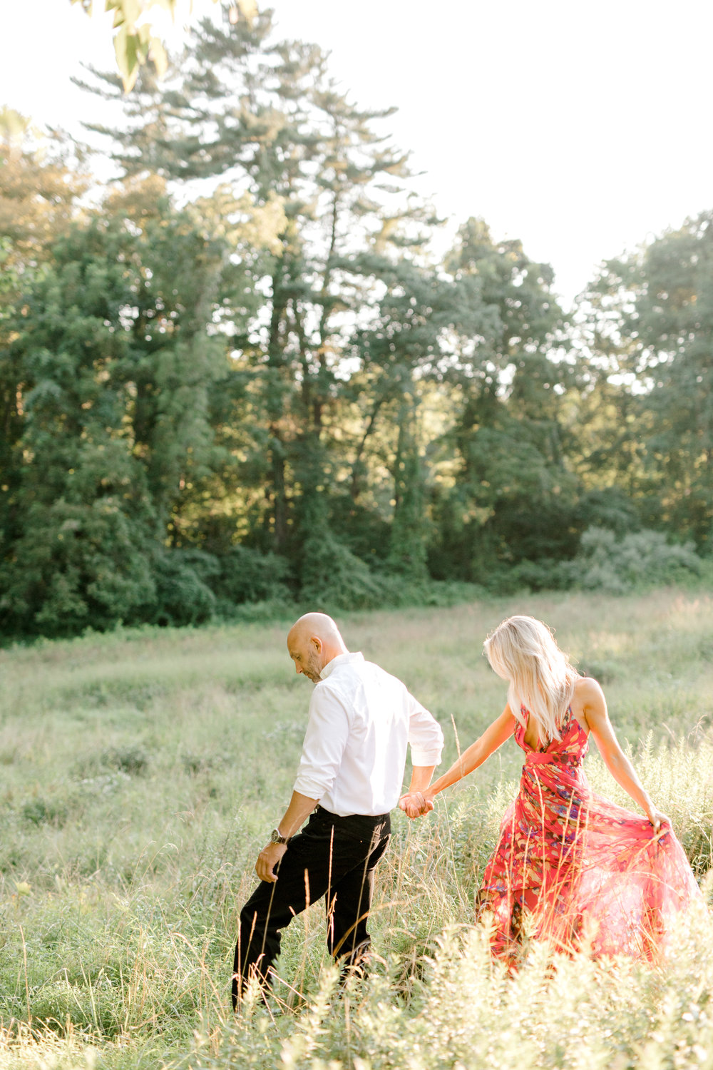 Bill leads Liz into a glowing sunlit field in an intimate moment for their romantic sunset woodland engagement session at Parque at Ridley Creek